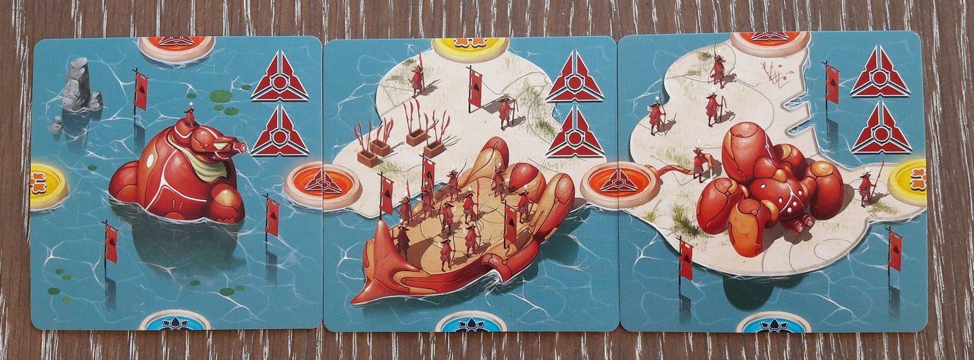 Les cartes îles.  3/5 : les bâtiments militaires. L'arsenal de Mû fait le grand écart entre le canon à énergie et la hallebarde.