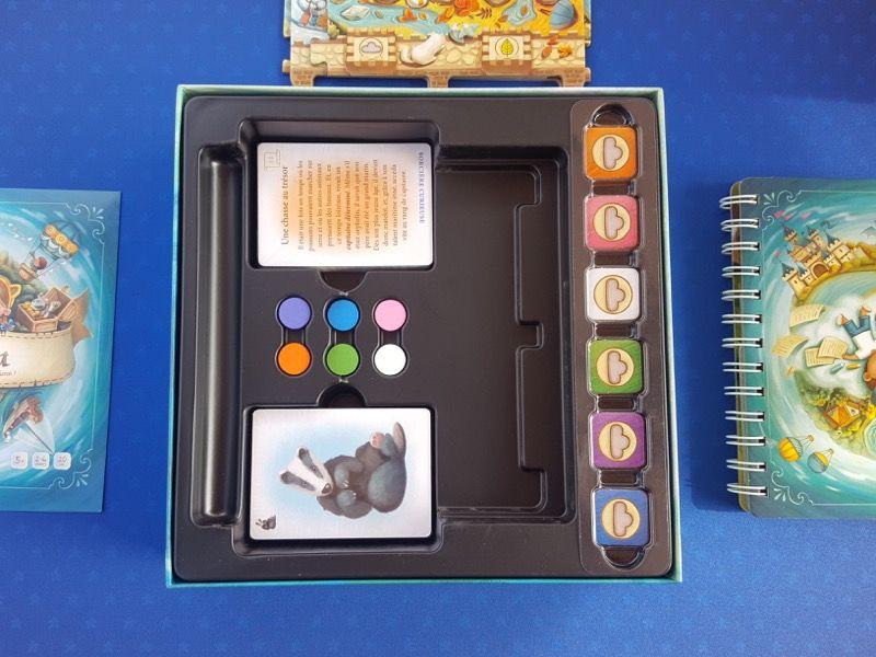 2 paquets de cartes sous blister, 6 pions en bois, des jetons de couleurs (orange, rose, blanc, vert, violet et bleu).