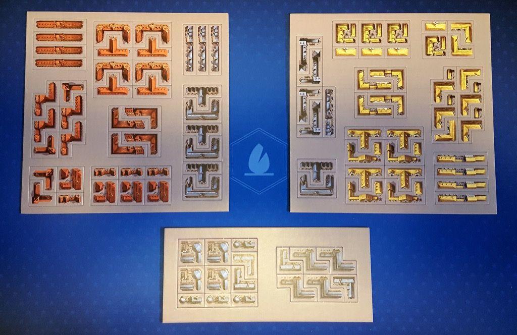 4 lots de tuiles contenant chacun huit bâtiments de trois couleurs différentes : rouge (administratif), bleu (industriel) et jaune (résidentiel).