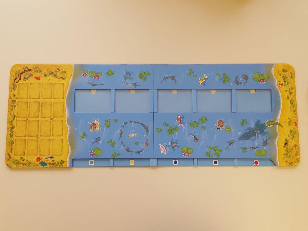 De gauche à droite : une zone pour placer les caisses de bananes, une zone pour insérer les cartes hippopotames et une zone de départ dans le sable.