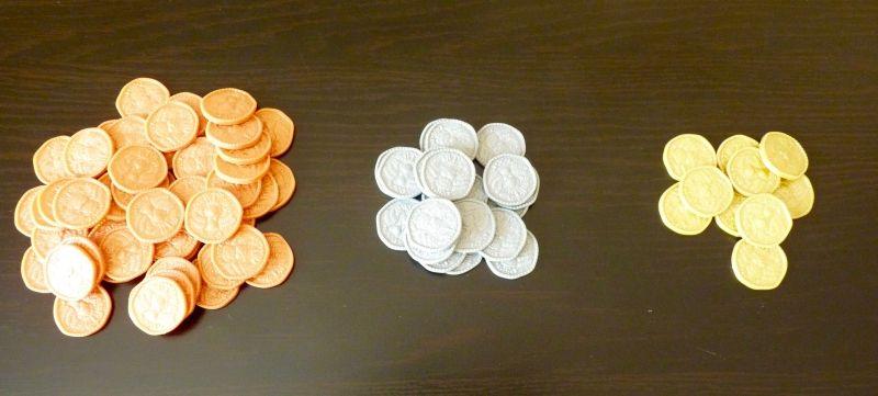 Les écus : 50 pièces de cuivre (1 écu), 20 pièces d'argent (5 écus) et 10 pièces d'or (10 écus).