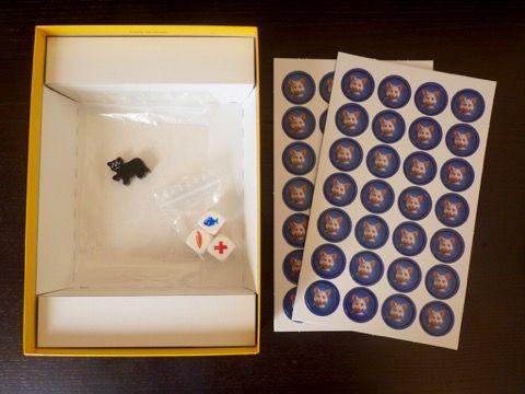 Un sachet avec 3 dés, un pion chat noir et 2 punchboards avec 56 jetons souris.