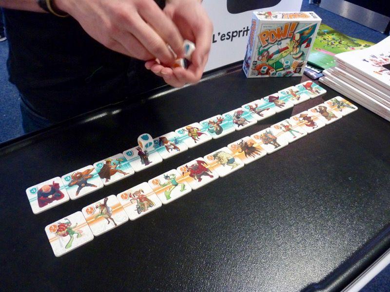 Pow ! une nouveauté ou presque... C'est une rethématisation de Sushi Bar de Reiner Knizia avec des dessins de super héros illustrés par Jonathan Aucomte.