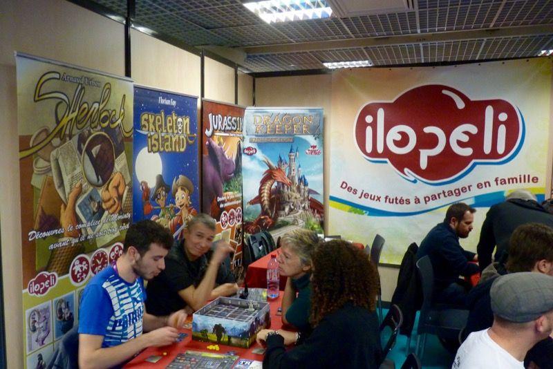 Après la partie je salue en face Arnaud Arbon le patron d'Ilopeli (de dos en train d'expliquer son jeu Dragon Keeper).