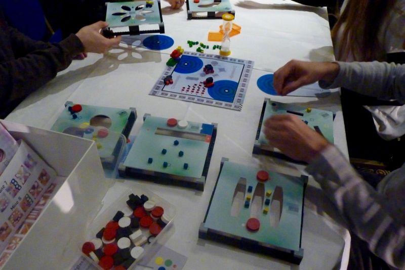 On est sur du matériel 3D. Il faut déplacer le plus rapidement les cubes sur les zones couleurs et pousser les pions rouges dans les trous.