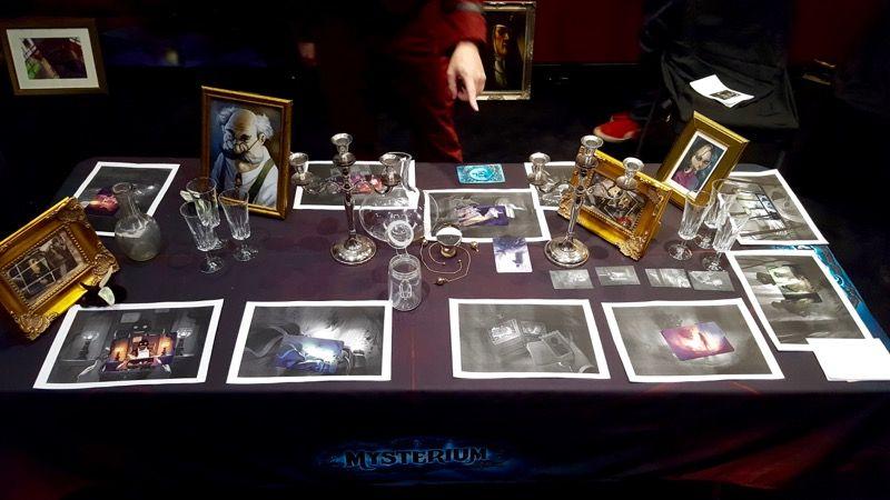 Les photos en noir et blanc avec les cartes protos en couleur sur la table : il faut trouver le mobile du crime.